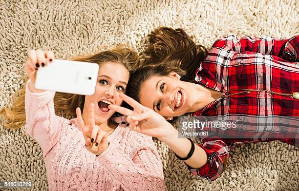 Two female friends taking a selfie with smartphone at home