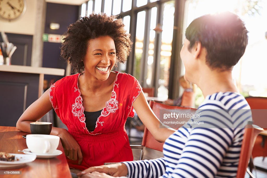 Two female friends talking at a coffee shop : Stock Photo
