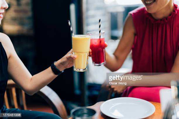 two female friends toasting drinks at restaurant - cocktail stock pictures, royalty-free photos & images
