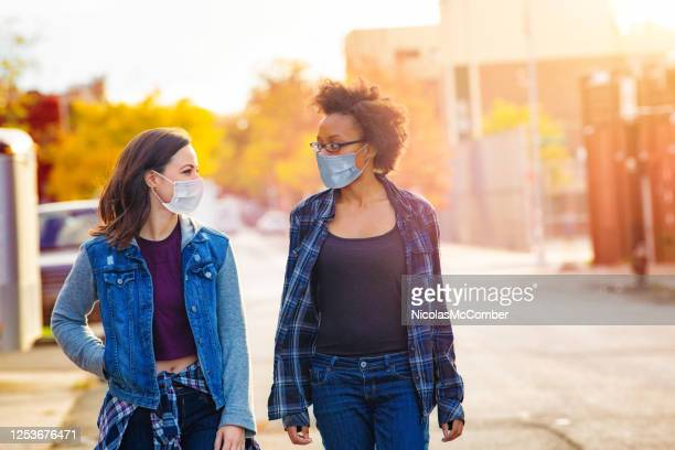 two female friends walking down a brooklyn alley wearing face masks - side by side stock pictures, royalty-free photos & images