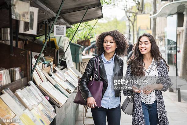 Two female friends walking past bookshop