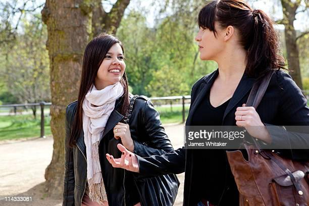Two female friends walking through park