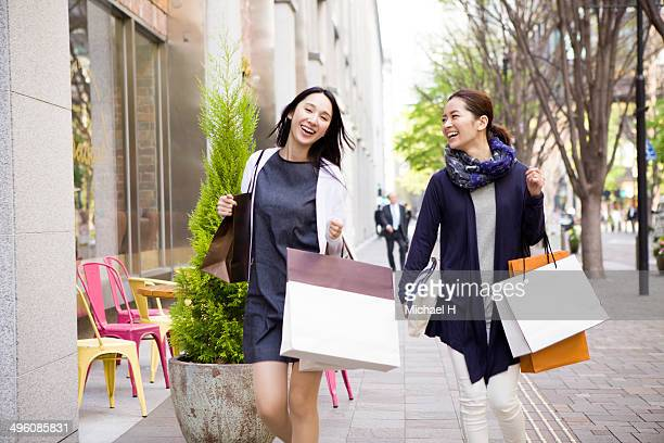 two female friends walking with shopping bags - 買い物袋 ストックフォトと画像