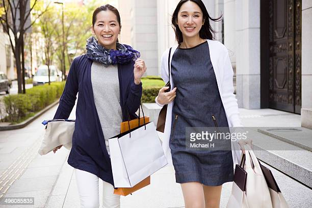 two female friends walking with shopping bags - 30代の女性 ストックフォトと画像