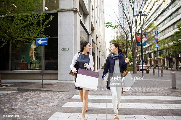 two female friends walking with shopping bags