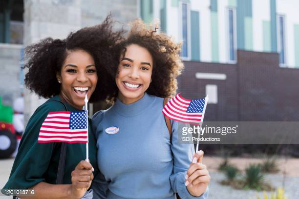 two female friends wave flags and smile after voting - vote stock pictures, royalty-free photos & images