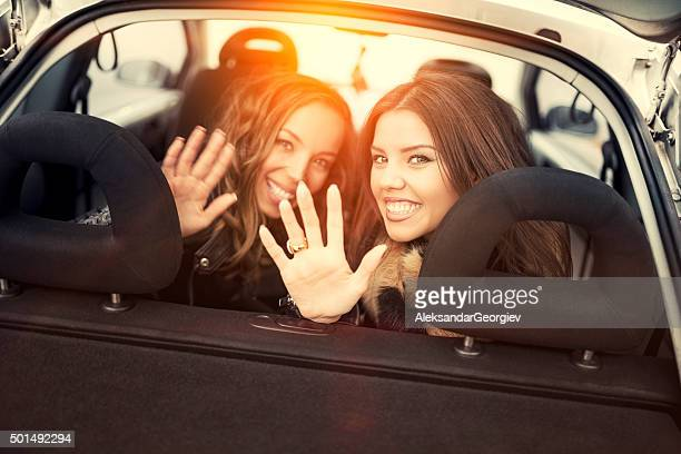 Two Female Friends Waving Goodbye from Back Seat