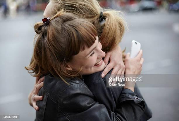 two female friends with cell phone hugging - weibliche freundschaft stock-fotos und bilder