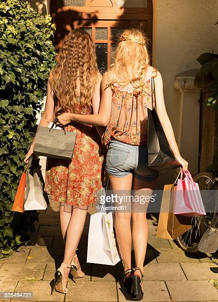 Two female friends with shopping bags, back view