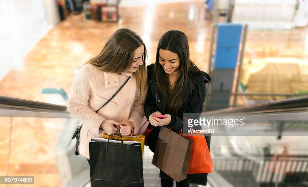 Two female friends with shopping bags on an escalator of a shopping center looking at smartphone