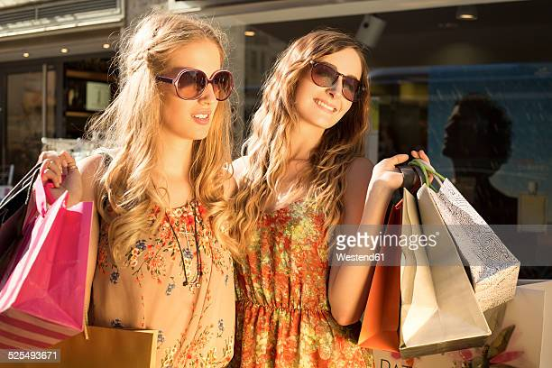 Two female friends with shopping bags standing in evening twilight