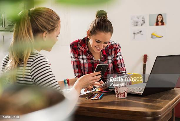 Two female friends with smartphone, laptop and digital tablet at home