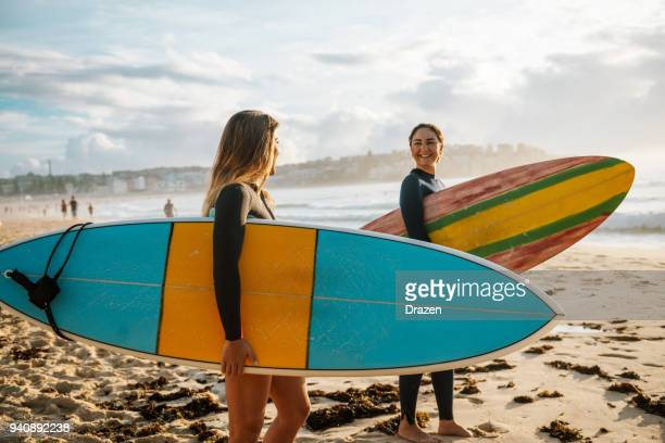 two female friends with surfboards - young adult photos stock photos and pictures