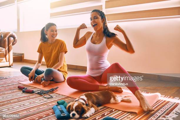two female friends working out and having fun together at home - showing off stock pictures, royalty-free photos & images