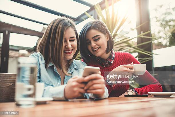 Two Female Frineds Holding Smartphone and Chatting in Coffee Shop