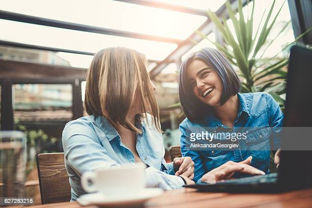 two female frineds using laptop and laughing in coffee shop - collègue photos et images de collection