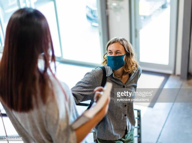 two female generation z college students wearing face masks standing on stairs holding onto railing - eyecrave  stock pictures, royalty-free photos & images