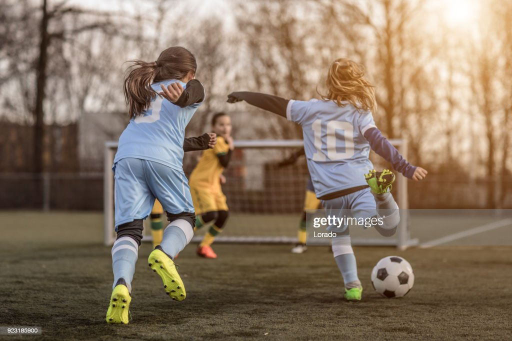Two Female Girl Soccer Teams playing a football training match in the Spring outdoors : Stock Photo