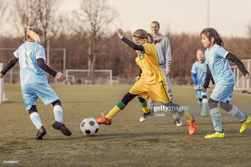 Two Female Girl Soccer Teams playing a football training match : Stock Photo