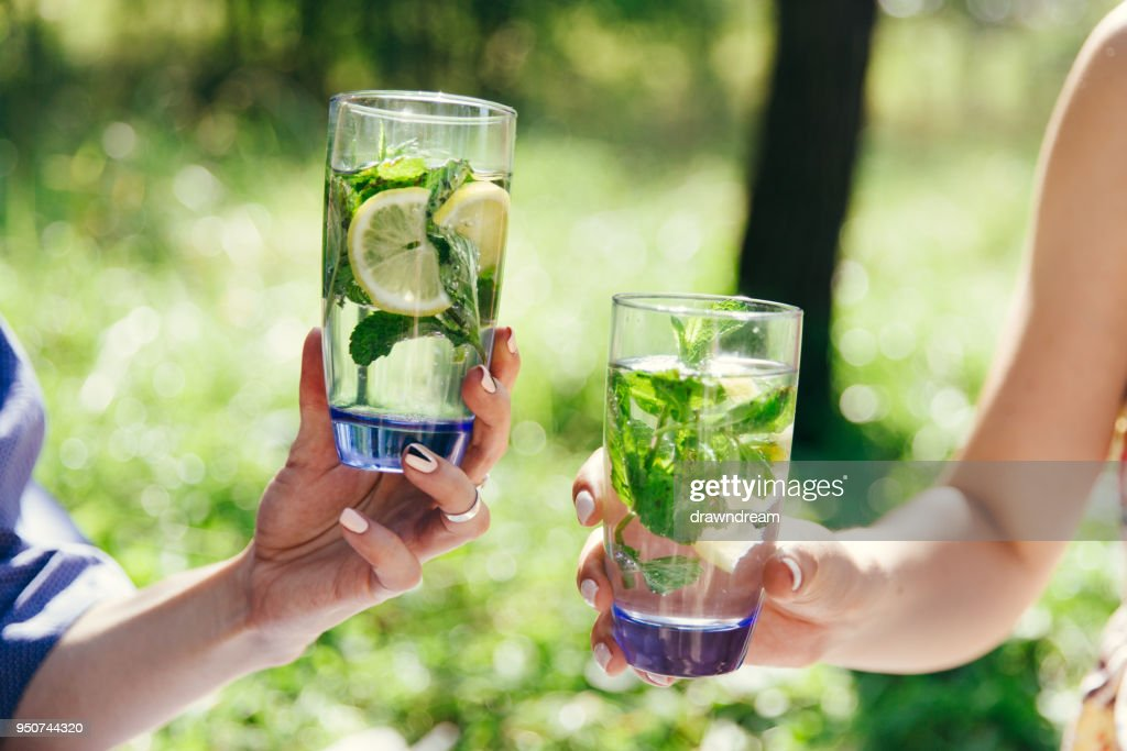 Two female hands holding glasses filled water with lemon and green mint leaves. Picnic in the garden. Detox, healthy eating, drinks, diet and people concept. Summer, outdoors. : Stock Photo