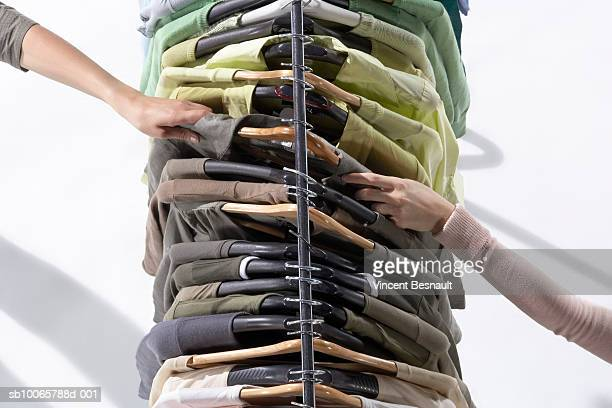 two female hands holding same shirt hanging from clothes rack - 衣料品店 ストックフォトと画像