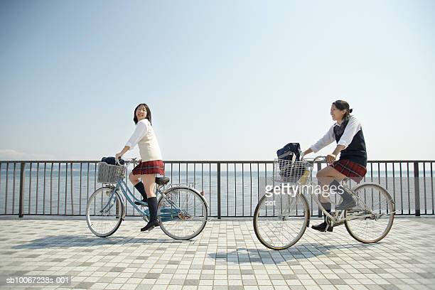 Two female high school students (17-18) riding bikes by seafront