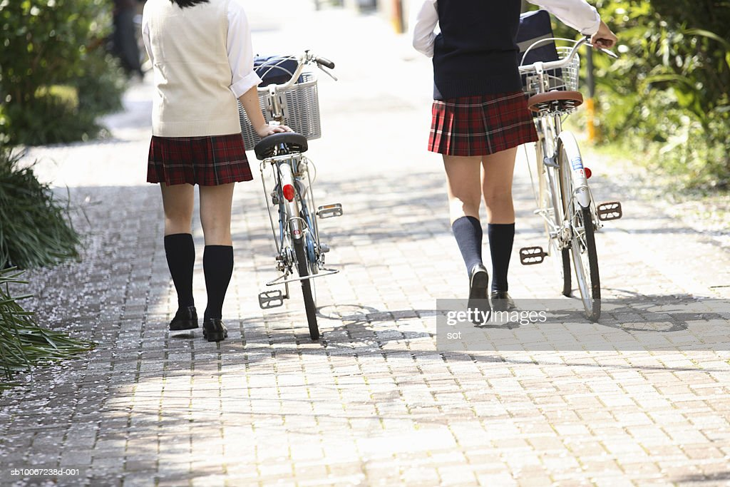 Two female high school students (17-18) walking with bicycles, rear view, low section : Stock Photo