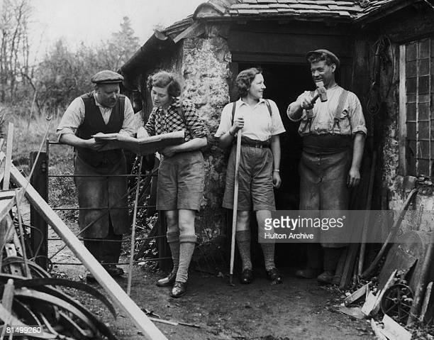 Two female hikers ask for directions from the village blacksmith and his mate, at Fittleworth in West Sussex, 2nd May 1936.