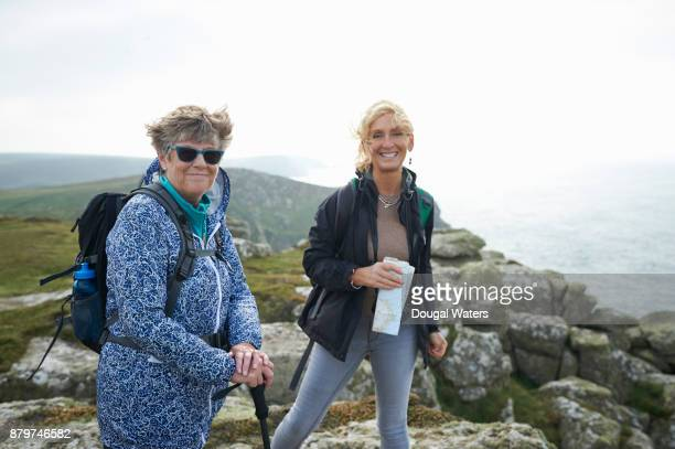 Two female hikers on a rocky Atlantic coastline.