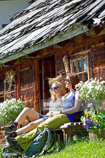 Two female hikers resting in mountain hut