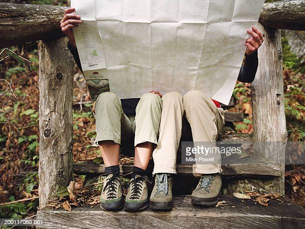 Two female hikers sitting on wooden steps, looking at map