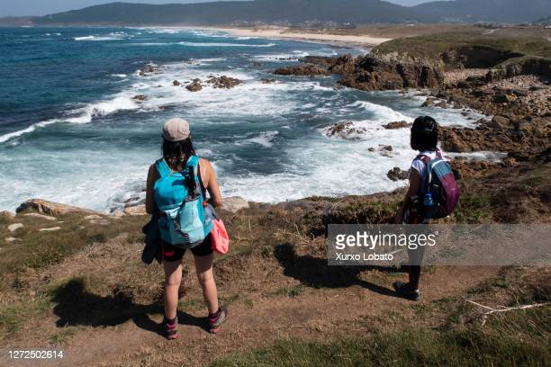 Two female hikers walk the path along the coast of cliffs and rocky beaches near Traba beach on September 12 Laxe, Galicia, Spain.