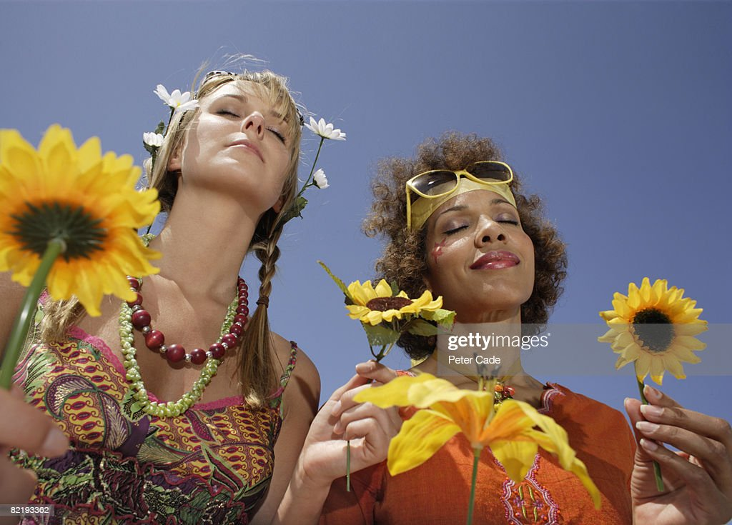 Two female hippies holding flowers : Stock Photo