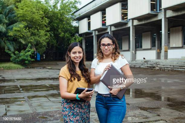 two female hispanic students proudly standing outside their university in cali colombia - cali colombia stock pictures, royalty-free photos & images