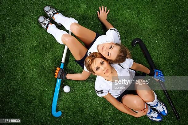 Zwei weibliche hockey-Spieler Sitzen im sport field