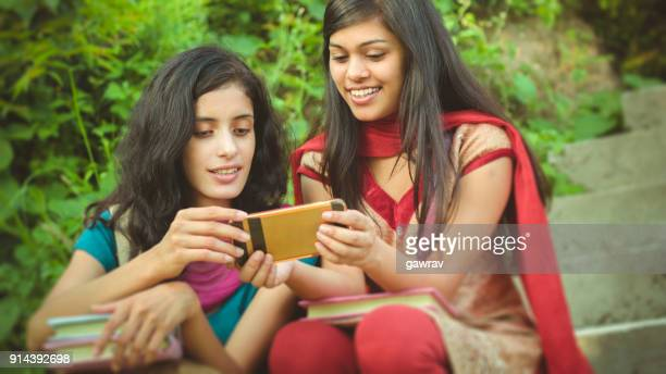 Two female Indian college students from rural background sharing smartphone.