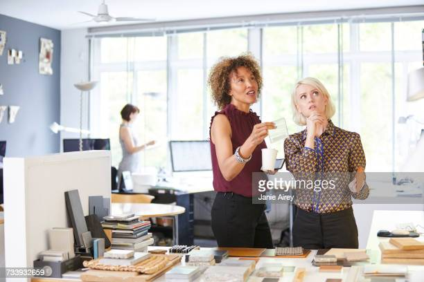 Two female interior designers considering swatches at office desk