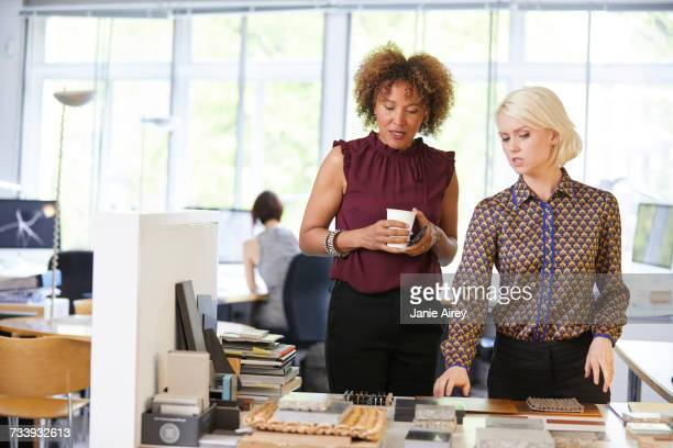 Two female interior designers looking at swatches at office desk