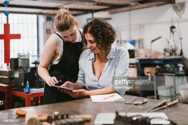 Two female jewellers looking at digital tablet at workbench