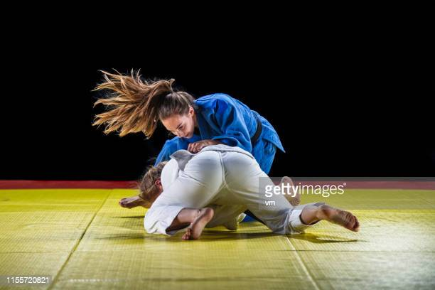 two female judo practitioners grappling on a tatami mat - judo stock pictures, royalty-free photos & images