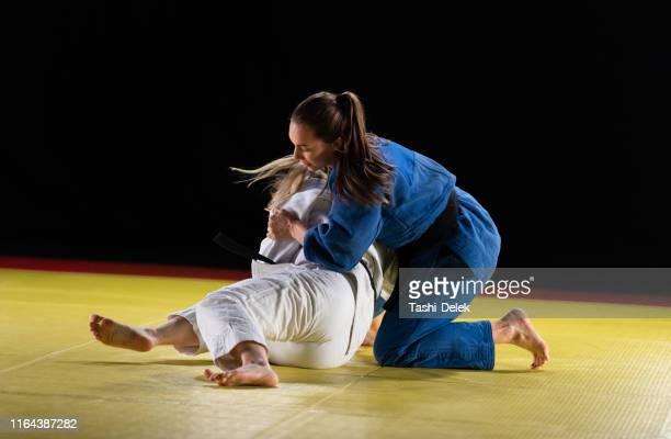 zwei judo-praktizierende grappling on a tatami mat - frauen ringen stock-fotos und bilder