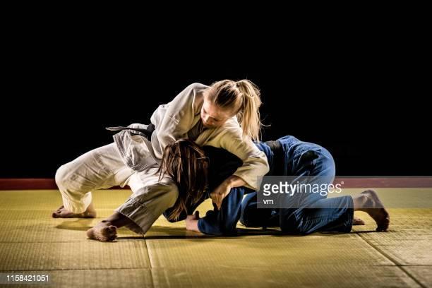 zwei judokas-frauen ringen auf einer tatamimatte - frauen ringen stock-fotos und bilder
