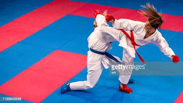 two female karate practitioners sparring on a tatami mat - taekwondo stock photos and pictures