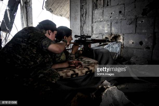 Two female kurdish fighters search for ISIS positions on the frontline of Raqqa In Summer 2017 the Syrian Democratic Forces launched a battle against...