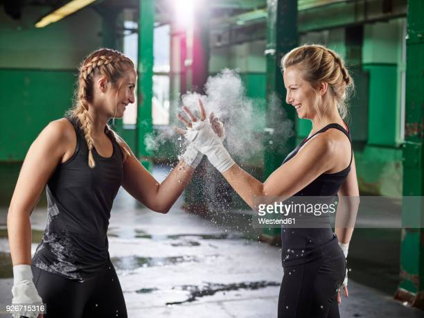 two female martial arts shaking hands after training - sports stock-fotos und bilder