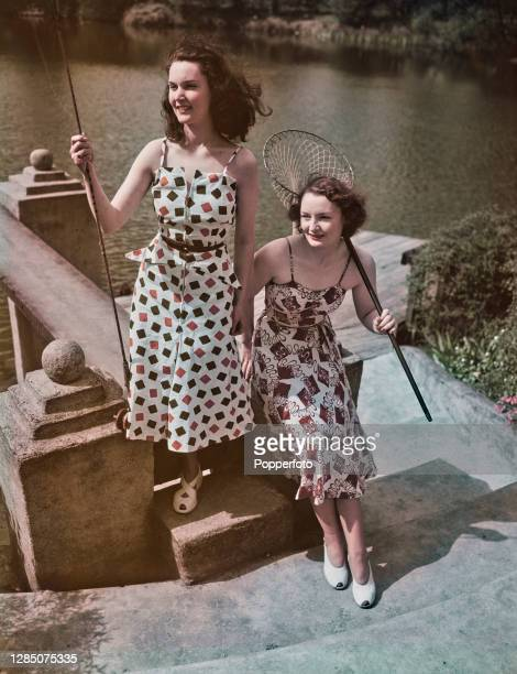 Two female models posed wearing informal patterned summer dresses with slender straps next to a lake in England in May 1949.