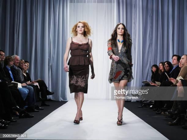 Two female models walking down runway