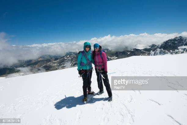 Two Female Mountaineers Smile on the summit of a glacier.