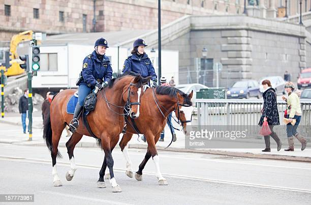 Two female mounted police clearing the road.