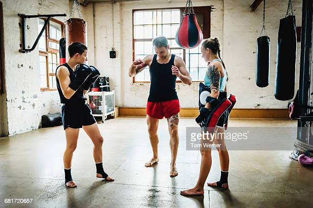 Two female muay thai boxers with trainer in gym